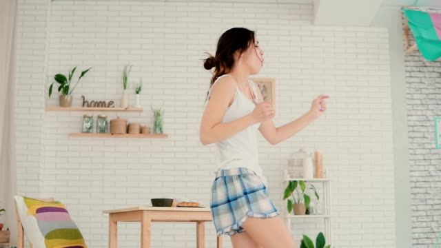 beautiful young woman in kitchen dancing in the morning. brunette girl wearing pajamas haves fun at home. slow motion - pajamas stock videos & royalty-free footage