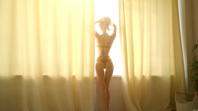 Beautiful young woman in lingerie stretching near the window at home.