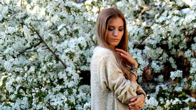リンゴの木の下で庭で咲いてロングドレス自由奔放に生きるスタイルの美しい若い女性 ビデオ