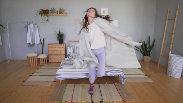 beautiful young woman in pajamas and a sweater is dancing and having fun next to the bed, hiding in a blanket in the bedroom. hygge or lagom concept - одна молодая женщина стоковые видео и кадры b-roll