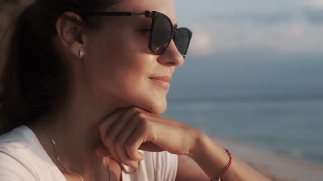Beautiful young woman in sunglasses watching sky and sunset.