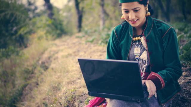schöne junge frau in traditioneller kleidung von kinnaur mit laptop. - ohrring stock-videos und b-roll-filmmaterial