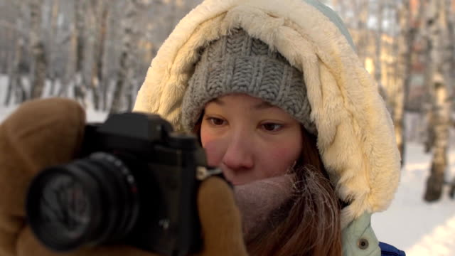 Beautiful young woman in winter clothing, mittens and wool hat photographing snowy forest by a knitted camera