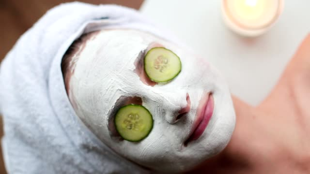 beautiful young woman is getting facial clay mask at spa, lying with cucumbers on eyes - cetriolo video stock e b–roll
