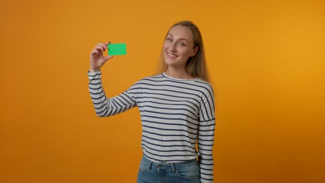 A beautiful young woman is smiling and holding a blank green card in her hand. A beautiful young woman is smiling and holding a blank green card in her hand. The concept of banking, credit card, business card holders. Yellow background. 4K video. business card stock videos & royalty-free footage