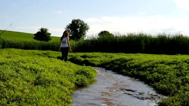 Bela jovem Jeans Curta a água natureza fundo de férias - vídeo
