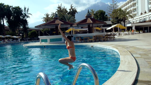 Beautiful young woman jumping into the swimming pool in hotel with splash of water. video