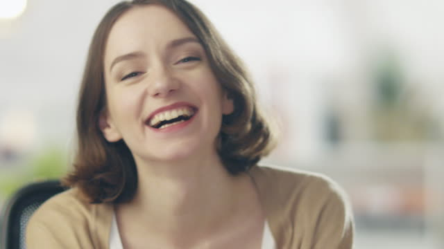 Beautiful Young Woman Laughs on the Camera. Her Background is Bright and Blurred. video