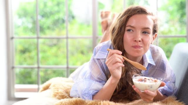 Una hermosa joven acostado en el sofá y comer yogur - vídeo