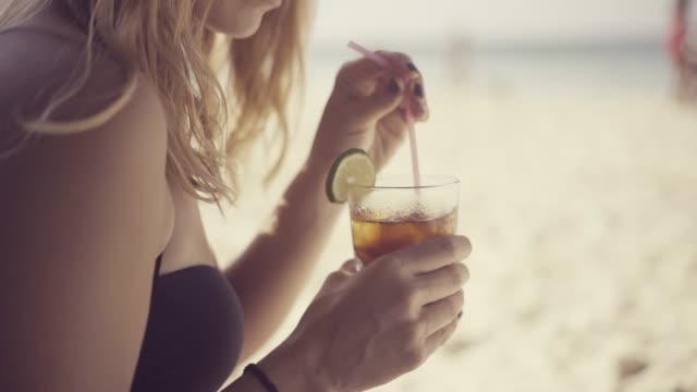 beautiful young woman mixing her cocktail with a plastic straw in a glass, decorated with a lime slice, on the beach on a hot warm summer day in the caribbean sea - rum superalcolico video stock e b–roll