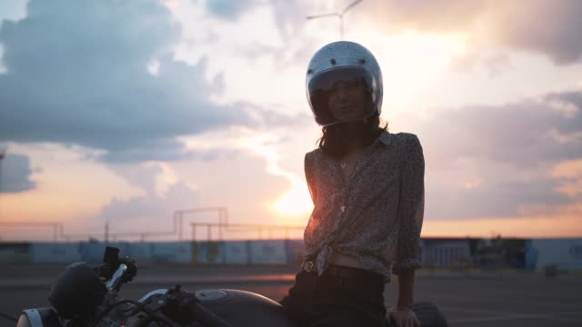 vídeos de stock e filmes b-roll de beautiful young woman motorcyclist with helmet on beautiful sunset sky background - helmet motorbike