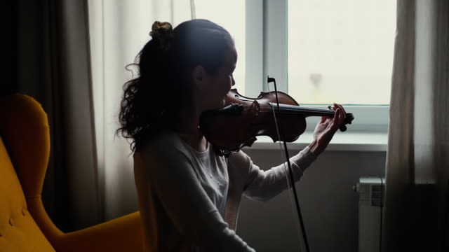 Beautiful young woman musician playing the violin by the window