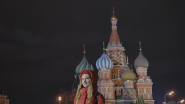Beautiful young woman on the Red Square at night is looking into the distance and smiling Beautiful young woman on the Red Square at night is looking into the distance and smiling. The background is Saint Basil's Cathedral. russian culture stock videos & royalty-free footage