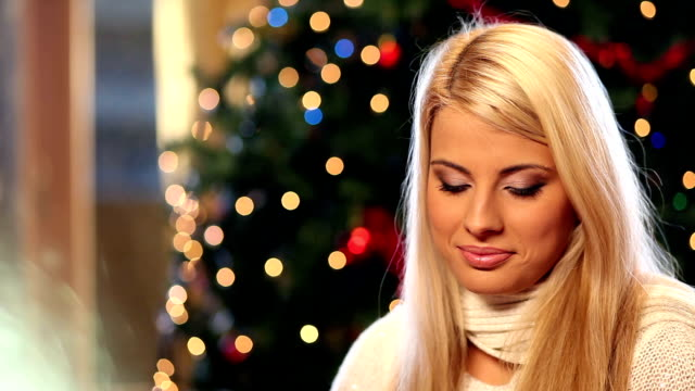 Beautiful young woman opening Christmas presents. video