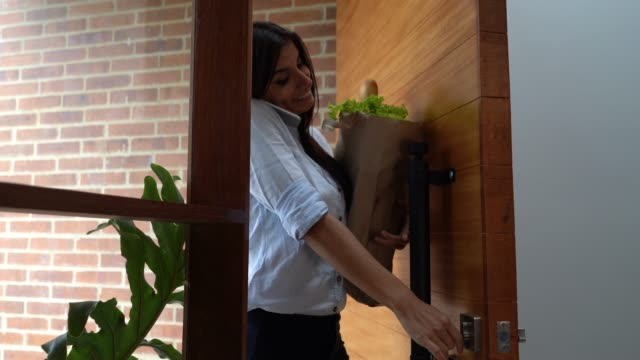 beautiful young woman opening door while talking on phone and carrying groceries - portare video stock e b–roll