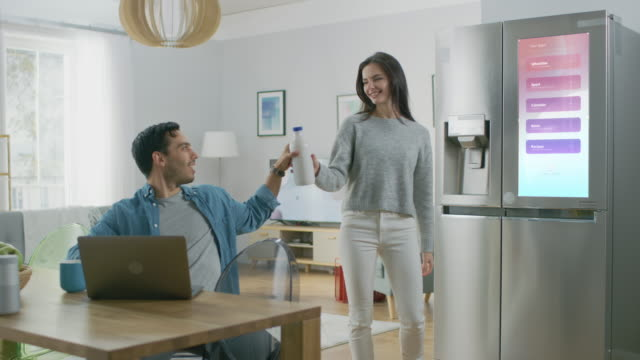 Beautiful Young Woman Opens the Fridge and Gives a Milk Bottle to Her Boyfriend. Then She Checks the Futuristic Digital To-Do List on the Smart Fridge Door.