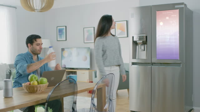 vídeos de stock e filmes b-roll de beautiful young woman opens the fridge and gives a milk bottle to her boyfriend. then she checks the futuristic digital to-do list on the smart fridge door. - frigorífico