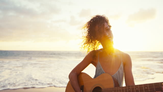 Beautiful young woman playing guitar on the beach at sunset video