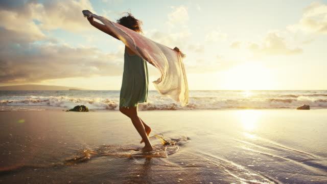 夕暮れ時のスローモーションでビーチで遊んで美しい若い女性 ビデオ