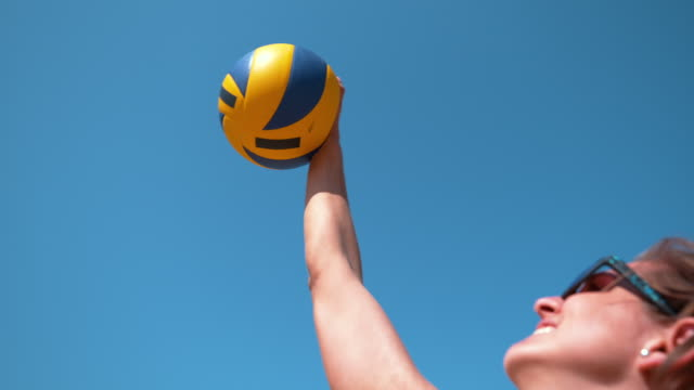 CLOSE UP: Beautiful young woman playing volleyball strikes the ball above head. SLOW MOTION, CLOSE UP, DOF: Beautiful young Caucasian woman playing volleyball strikes the ball above her head on a sunny day. Girl wearing blue sunglasses serves the ball during beach volleyball game volleyball sport stock videos & royalty-free footage