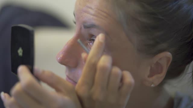 vídeos de stock e filmes b-roll de beautiful young woman plucks eyebrows, closeup. - puxar cabelos