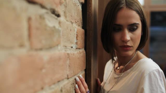 Beautiful young woman posing near brick wall
