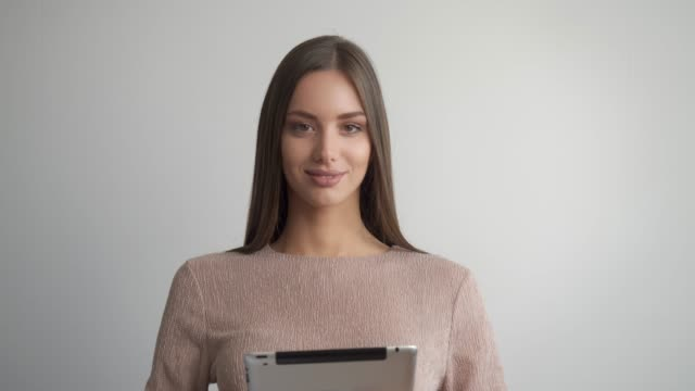 Beautiful young woman presenting while holding digital device. video
