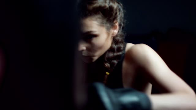 Beautiful young woman punching bag in fitness studio. Boxing in slowmotion.