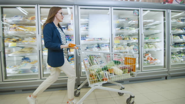 beautiful young woman pushes shopping cart full of goods through frozen goods and dairy section of the supermarket. moving side view shot. - замороженные продукты стоковые видео и кадры b-roll