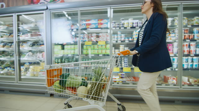 Beautiful Young Woman Pushes Shopping Cart full of Healthy Products Through Frozen Goods and Dairy Section of the Supermarket. Moving Side View Shot. Beautiful Young Woman Pushes Shopping Cart full of Healthy Products Through Frozen Goods and Dairy Section of the Supermarket. Moving Side View Shot. Shot on RED EPIC-W 8K Helium Cinema Camera. freezer stock videos & royalty-free footage