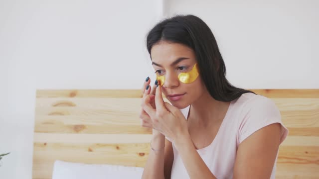beautiful young woman put patches under the eyes to care for the skin in the eye circle at home - sotto video stock e b–roll