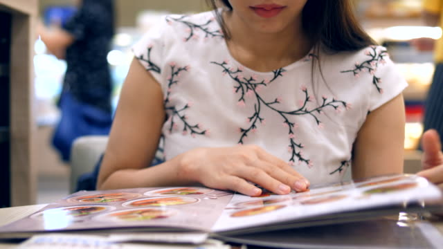 Beautiful young woman reading the menu Women, One Woman Only, 20-29 Years, 25-29 Years, Adult menu stock videos & royalty-free footage