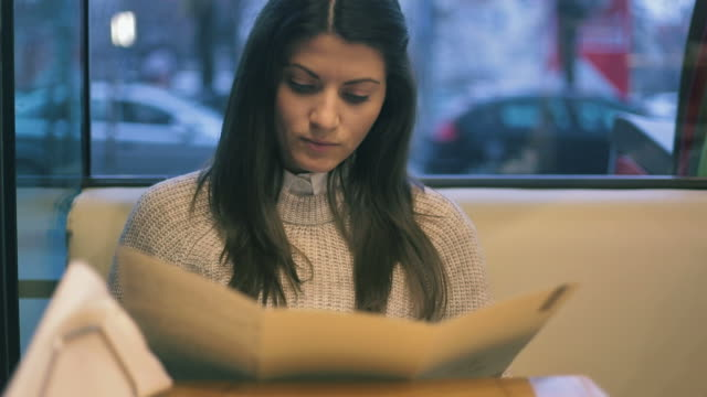 Beautiful young woman reading the menu. Beautiful young woman reading the menu while sitting at the table. Street view behind her. menu stock videos & royalty-free footage