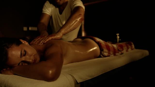 stockvideo's en b-roll-footage met mooie jonge vrouw reciving massage in de spa - massagetherapeut