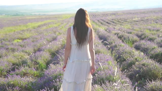 beautiful young woman relaxing and having fun on purple flower lavender field - wschodnio europejski filmów i materiałów b-roll