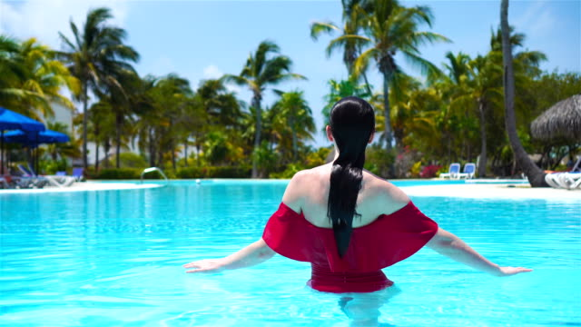 Beautiful young woman relaxing in swimming pool. Happy girl in outdoor pool at luxury hotel video