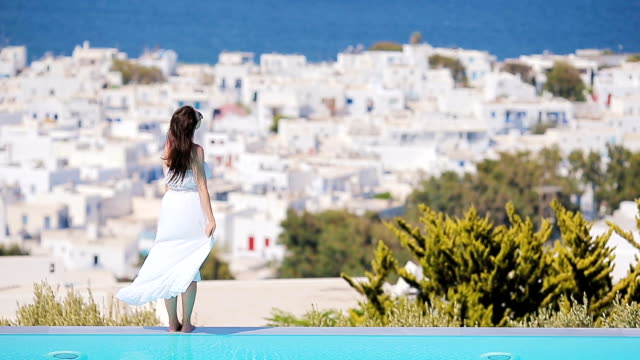 Beautiful young woman relaxing near pool with amazing view on Mykonos, Greece Beautiful woman enjoying summer vacation near pool aegean islands stock videos & royalty-free footage