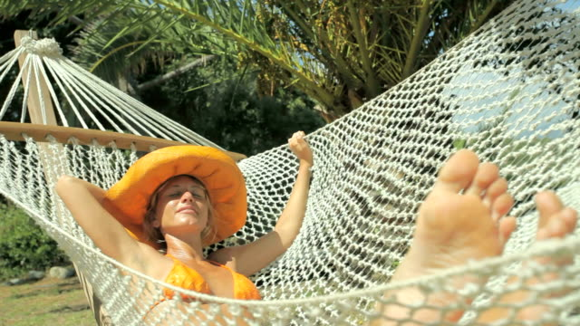 Beautiful young woman relaxing on hammock (series) video