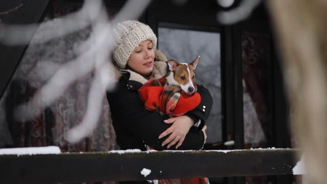 vídeos y material grabado en eventos de stock de hermosa joven se relaja en vacaciones de invierno con su perro - abrigo