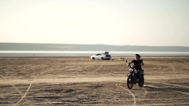 美麗的年輕女子,騎一輛摩托車騎上舊摩托車和做一個把戲。在日出或日落時的沙漠。女騎自行車的人。 - {{asset.href}} 個影片檔及 b 捲影像