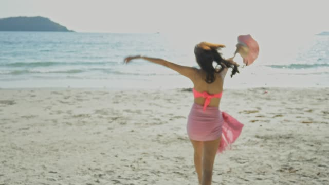 vidéos et rushes de belle jeune femme courant dans l'eau de mer sur la plage - mince