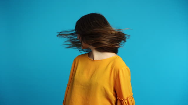 Beautiful young woman shaking head with long hair in slow motion Beautiful young woman shaking head with long hair in slow motion on blue background hair stock videos & royalty-free footage