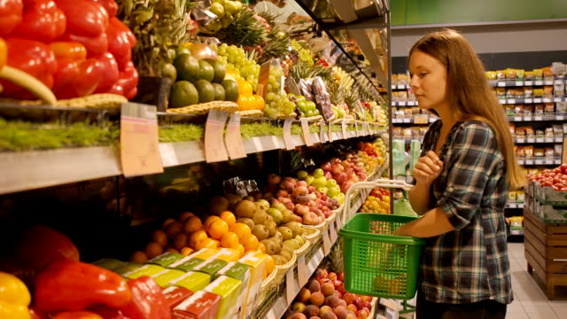 Beautiful young woman shopping for fruits products at a supermarket video