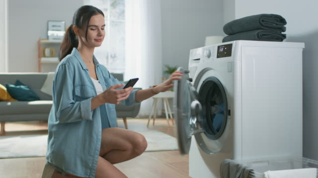 Beautiful Young Woman Sits on Her Knees Next to the Washing Machine. She Loaded the Washer with Dirty Laundry While Using Her Smartphone. Shot in Living Room with Modern Interior.