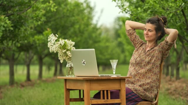 Beautiful young woman sitting at a desk using a computer in a field. video