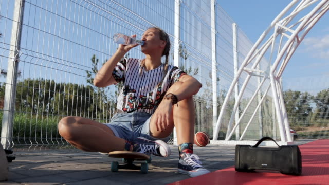 Beautiful young woman sitting on skateboard and drinking a water on sunny day