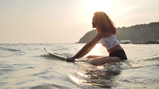 schöne junge frau sitzt auf dem surfbrett und wartet die wellen. sport cinemagramme - sprung wassersport stock-videos und b-roll-filmmaterial