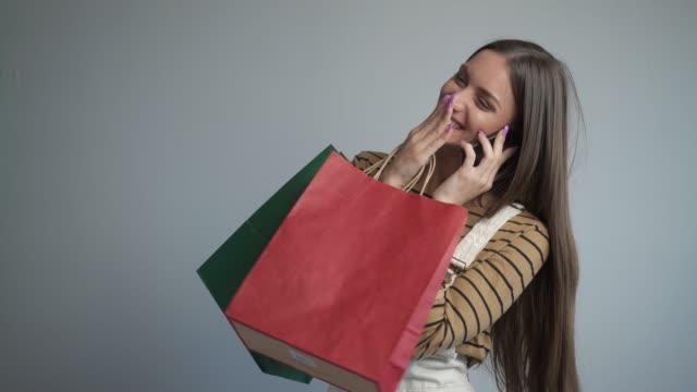 vídeos y material grabado en eventos de stock de hermosa joven sonriendo a la cámara sosteniendo una bolsa de compras y un teléfono inteligente. - shopping bags
