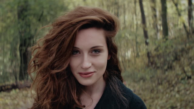 Beautiful young woman standing and smiling in forest Young smiling woman with curly red long hair wearing dark coat, standing in forest during an autumn day. 90fps redhead stock videos & royalty-free footage