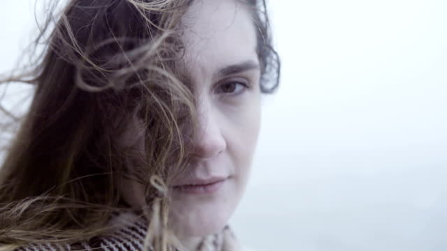 Beautiful young woman standing outdoor in foggy day and looking at camera. Hair of sad pensive woman waves on wind video